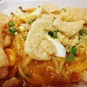 Pancit Palabok - Rice noodles smothered in a savory sauce and topped with toasted garlic, green onion, hard boiled egg, and chicharon (pork rinds)